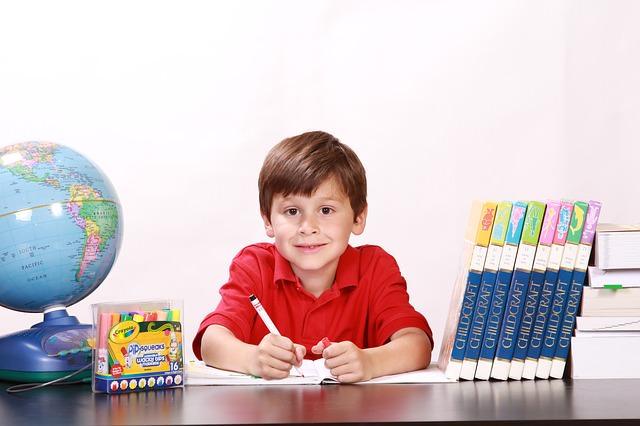 Uśmiechnięte dziecko uczy się przy biurku