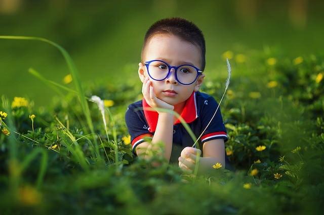 chłopiec w okularach na łące