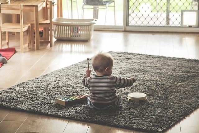 Dziecko siedzące na dywanie i grające