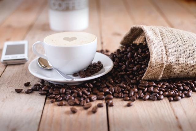 Filiżanka kawy i rozsypane ziarna