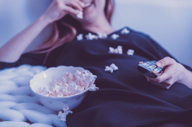 Kobieta je popcorn przed telewizorem