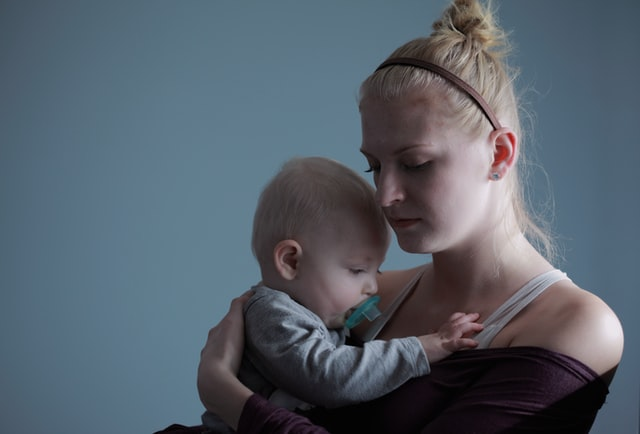 Młoda mama z dzieckiem na rękach